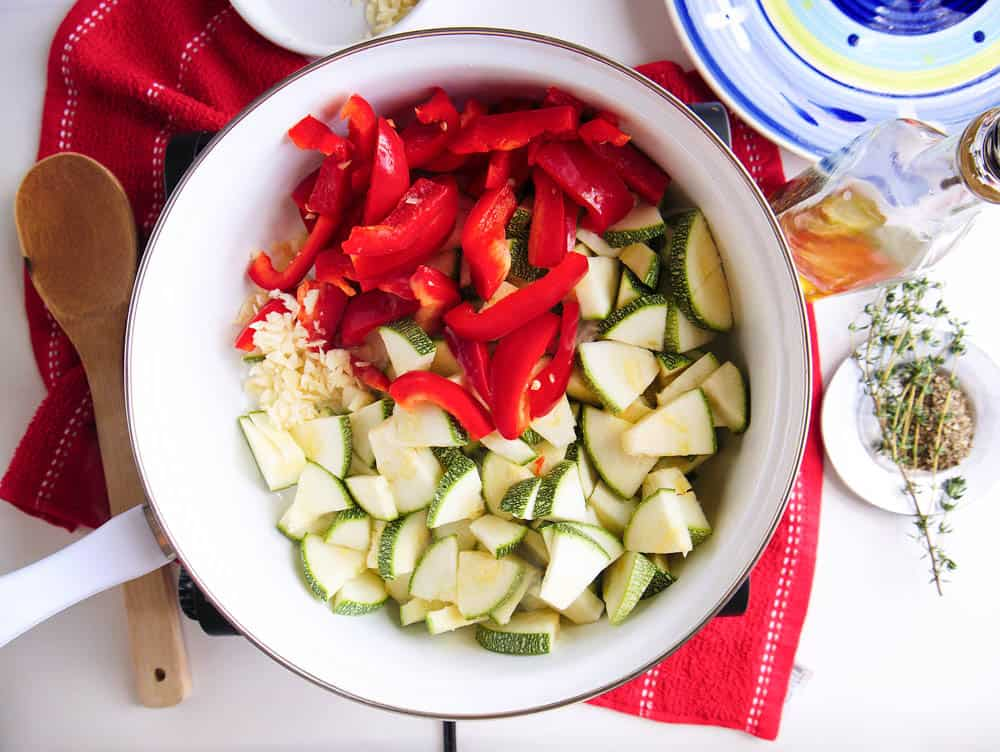 zucchini and red peppers added to the pan