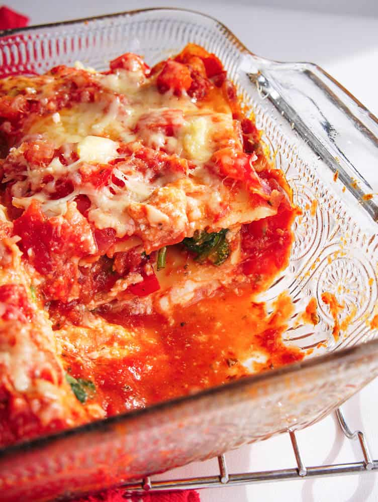 A portion of healthy veggie lasagna cut out of the casserole dish