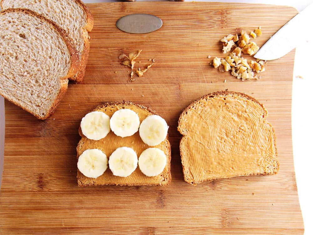 Peanut butter spread on bread and banana slices laid on top