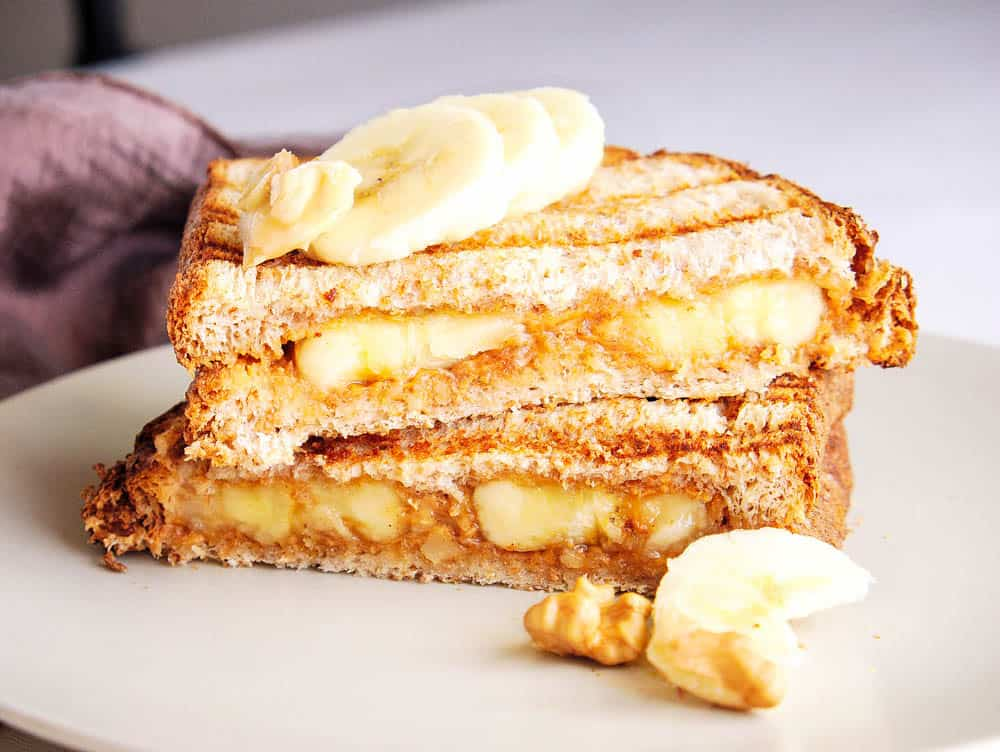 Two halves of a banana peanut butter sandwich stacked on top of each other
