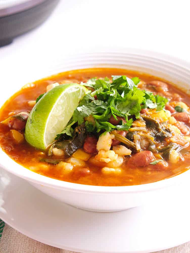 Instant Pot Pinto Beans Vegan Posole served in a white bowl with a lemon wedge and cilantro