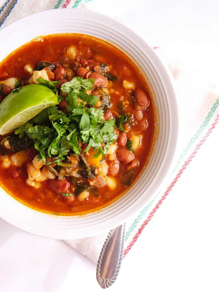 Instant Pot Pinto Beans Vegan Posole in a white bowl served with a spoon