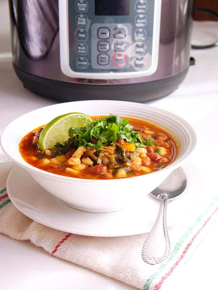 A bowl of Instant Pot Pinto Beans Vegan Posole in front of an Instant pot