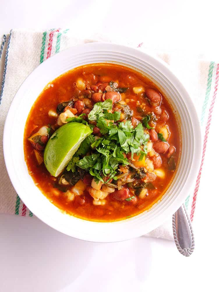 Instant Pot Pinto Beans Vegan Posole in a white bowl with fresh toppings and garnish