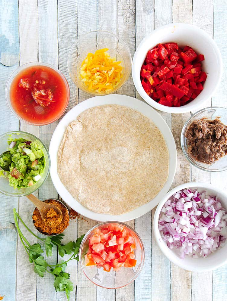 ingredients for mexican pizza: tortilla, cheese, bell pepper, taco seasoning, salsa, guacamole, tomatoes, onions, refried black beans