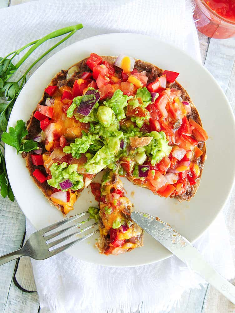 Healthy Copycat Taco Bell Mexican Pizza topped with salsa and guacamole, served on a white plate with a slice cut using a knife and fork