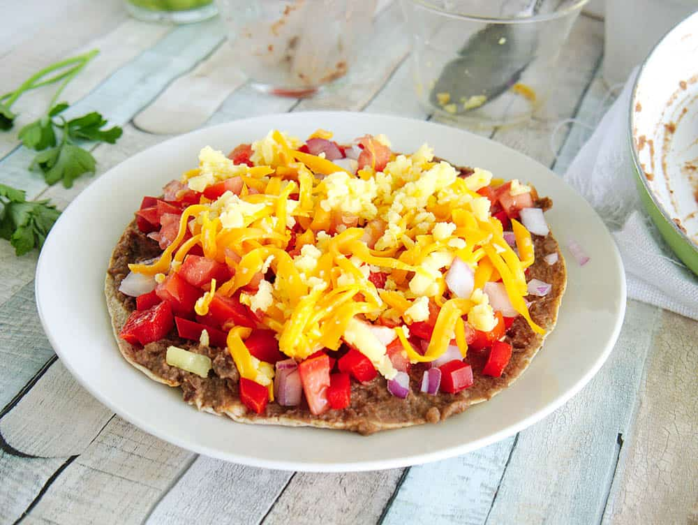 in process mexican pizza: topped with refried black beans, tomatoes, onions, bell peppers and cheese - served on a white plate
