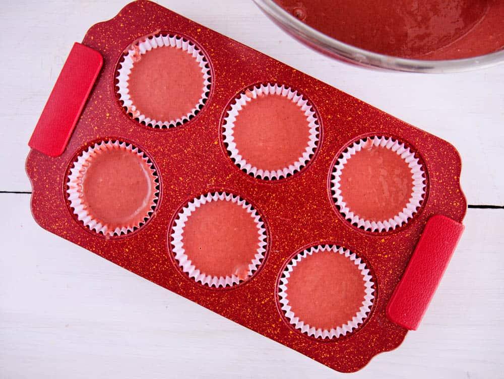 red velvet cupcake batter divided evenly among lined cups, filling each three-quarters full.