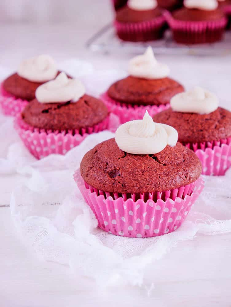 red velvet cupcakes with natural food coloring, with a pink cupcake wrapper against a white background