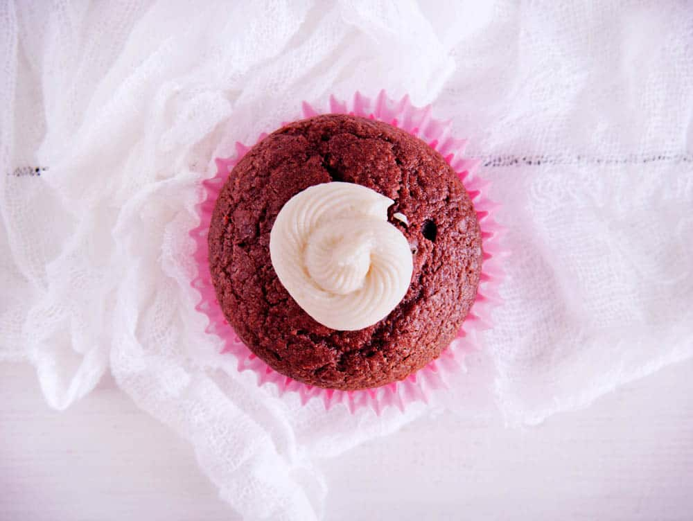 overhead view of a red velvet cupcake with natural food coloring, with a pink cupcake wrapper against a white background