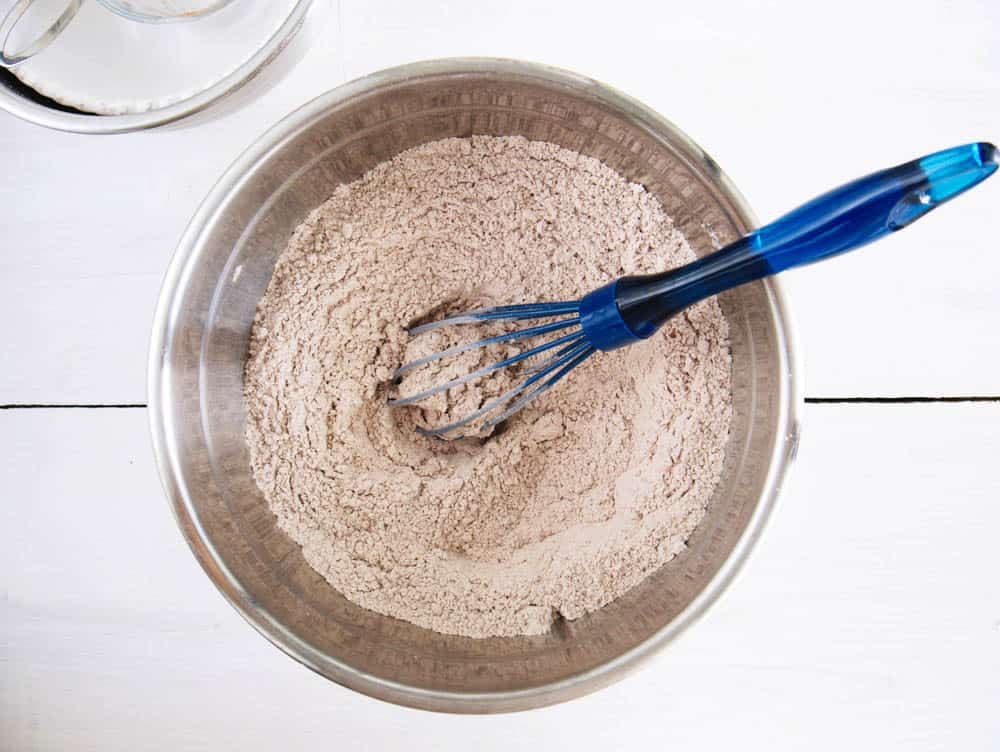 Flours, cocoa and salt whisked together in a large silver mixing bowl.