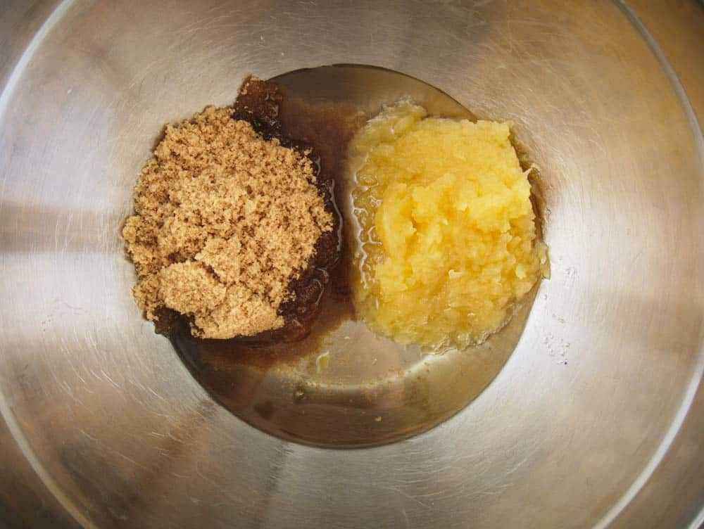 sugar, applesauce and oil combined in a silver mixing bowl