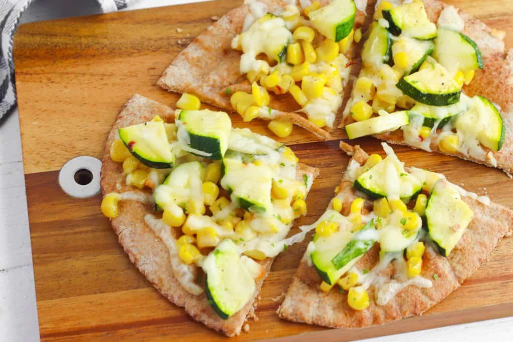 Vegetarian Corn and Zucchini Flatbread on a wooden cutting board