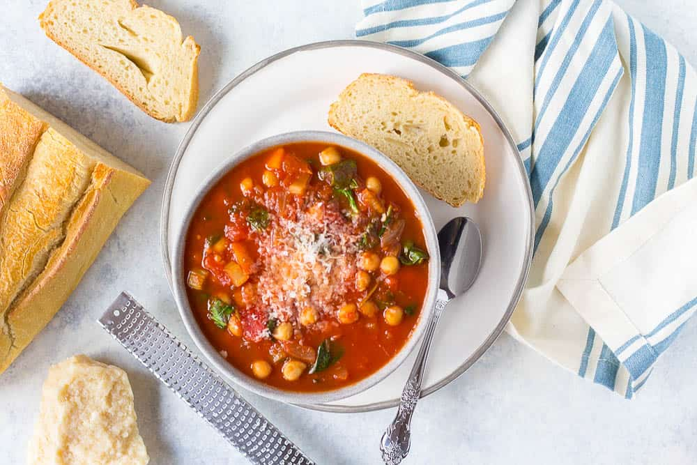Top shot of Italian chickpea soup served in a white bowl with crusty bread
