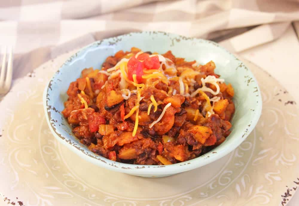 Spicy sweet potato breakfast hash topped with shredded cheese