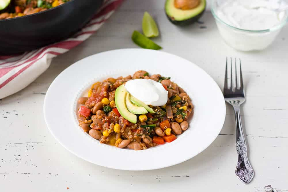 Mexican Taco casserole served in a white bowl with avocado and sour cream
