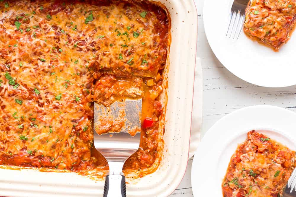 zucchini lasagna served on two white plates with a spatula in he casserole dish