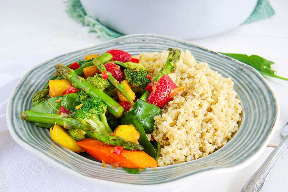 Healthy vegetable stir fry sauce with veggie and tofu served on a plate with quinoa