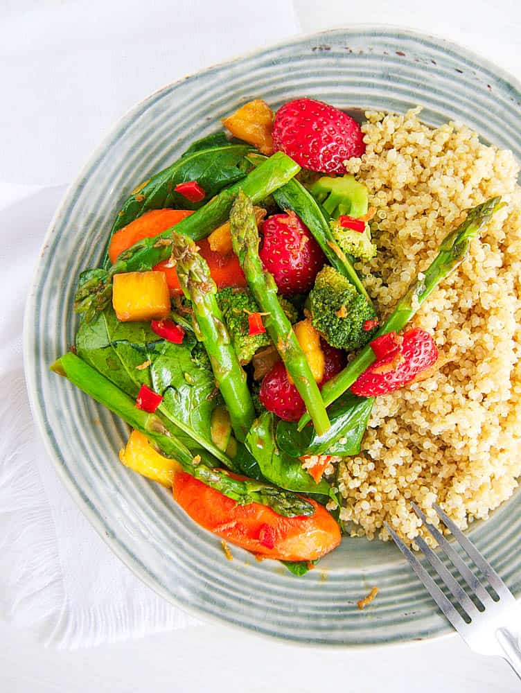 Healthy vegetable stir fry sauce with veggies served with quinoa on a glass plate