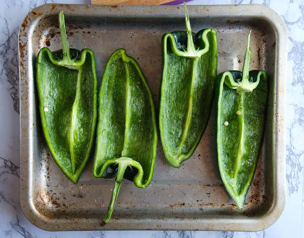 raw poblano peppers, cut in half and seeded on a metal oven tray