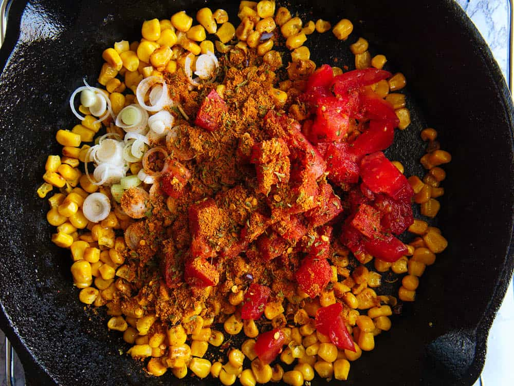 corn, scallions, tomatoes, taco seasoning being cooked in a cast iron skillet, top view