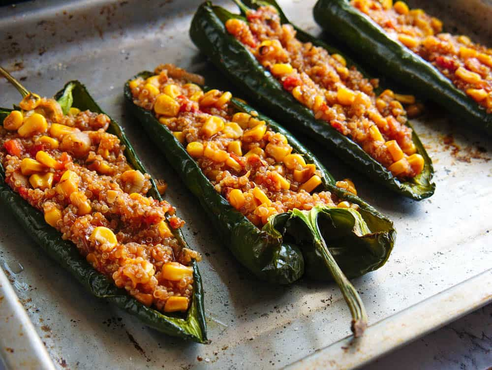 vegetarian stuffed poblano peppers on a metal sheet pan