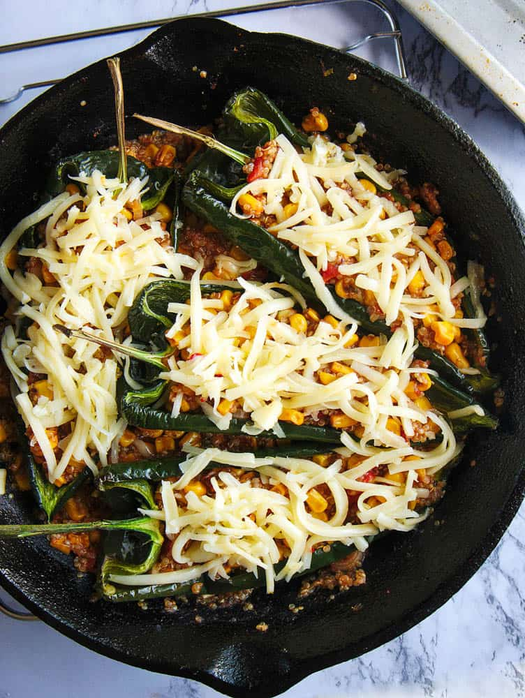 cheese added to vegetarian stuffed poblano peppers, right before going into the oven, placed in a cast iron skillet