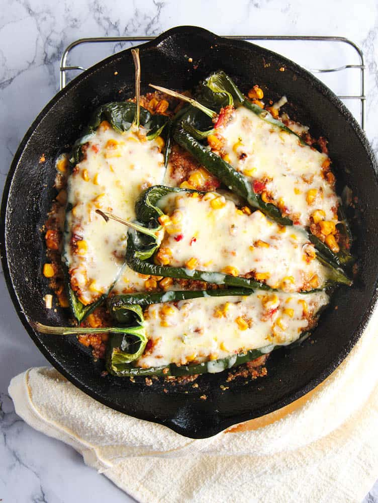 vegetarian stuffed poblano peppers with melted cheese on top, served in a cast iron skillet - top view
