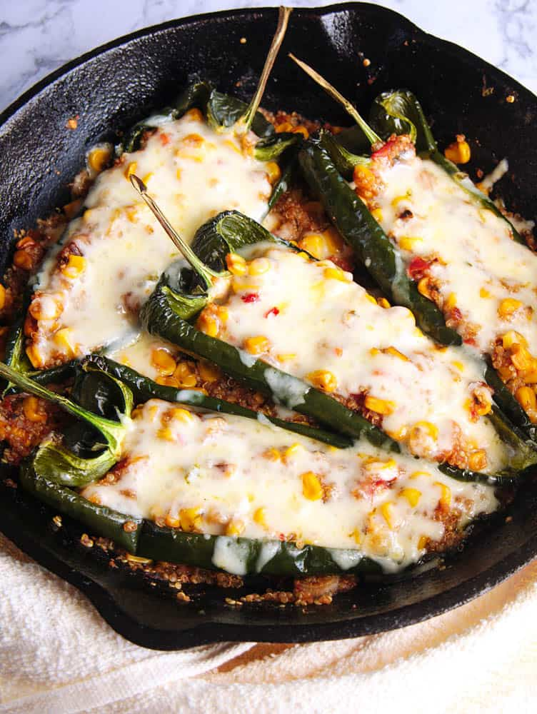 vegetarian stuffed poblanos with melted cheese on top, served in a cast iron skillet - top view