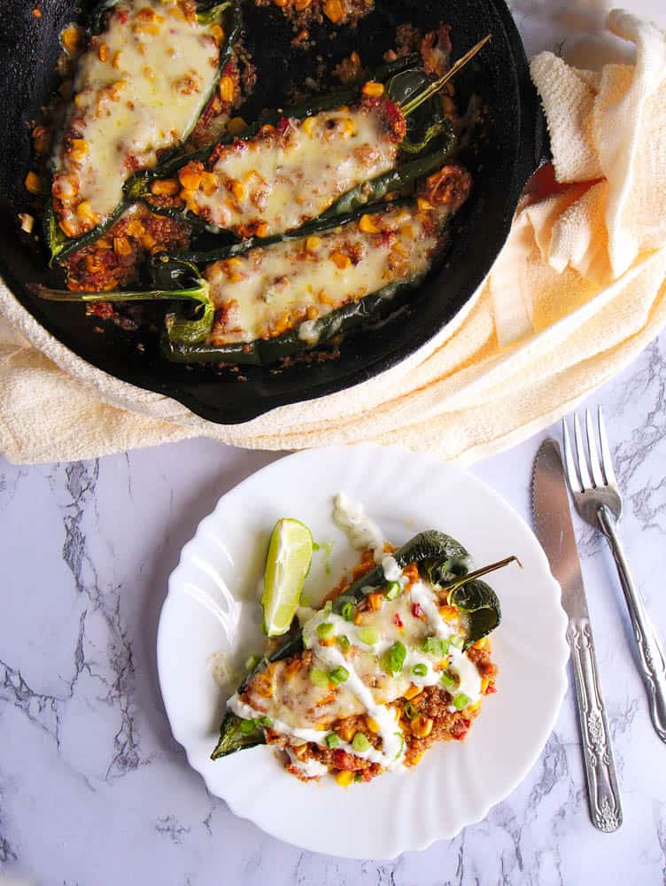 vegetarian stuffed poblano peppers with melted cheese on top, served in a cast iron skillet with one served on a white plate on the side - drizzled with sour cream, topped with chives, lime wedge on the side - top view