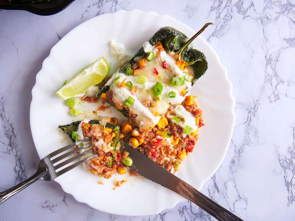 vegetarian stuffed poblano pepper with melted cheese on top, single serving on a white plate with a lime wedge, sour cream drizzle and diced green onions on top, cut into with a knife and fork
