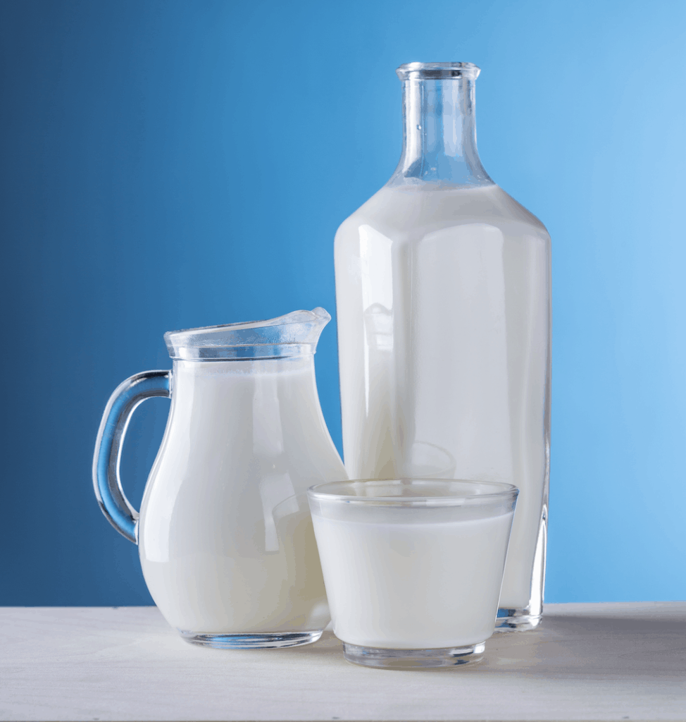 healthiest drinks for your child: milk in a glass pitcher pictured against a blue background
