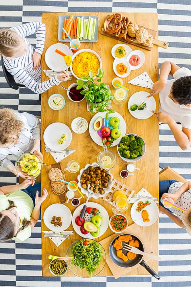 raising a kid who loves vegetables: Top view on table with food. Group of kids eating healthy dinner with vegetables