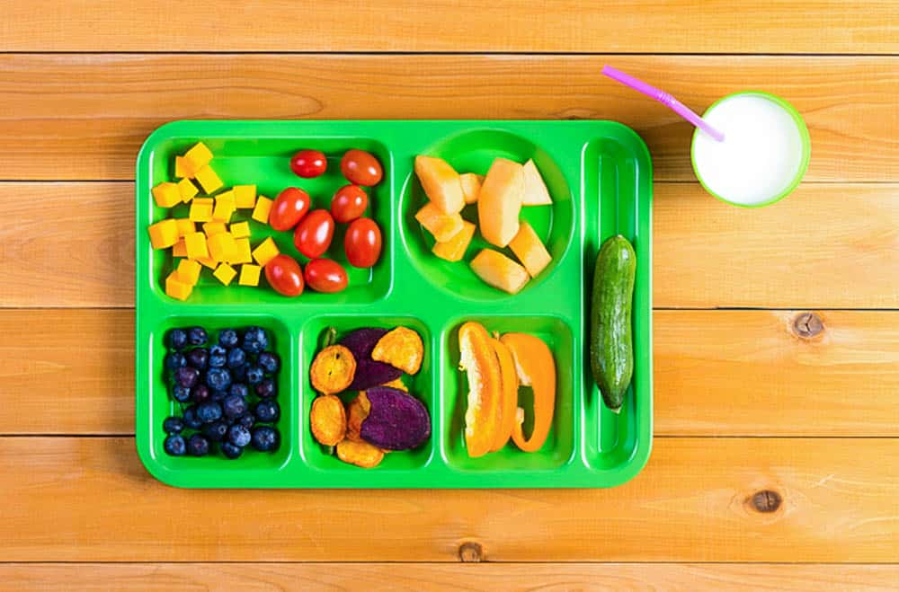 raising a kid who loves vegetables: green lunch tray with a variety of fruits and veggies, against a wood background