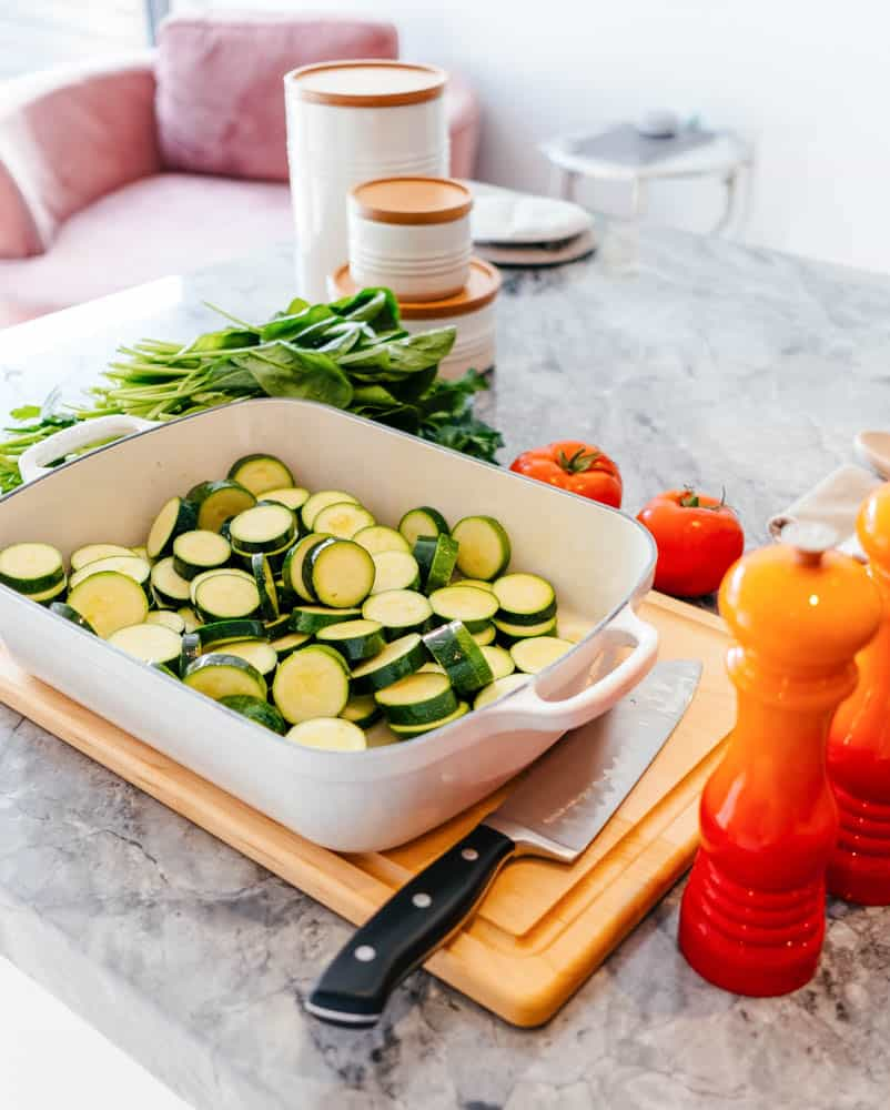 raising a kid who loves vegetables: sliced zucchini in a white porcelain baking dish, on a marble countertop
