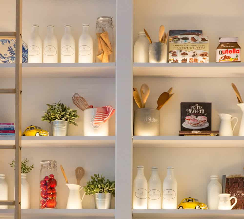 white wood pantry shelves with food storage containers