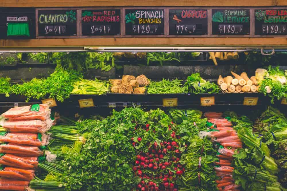 photo of produce at the grocery store: cilantro, radishes, spinach, carrots, romaine lettuce