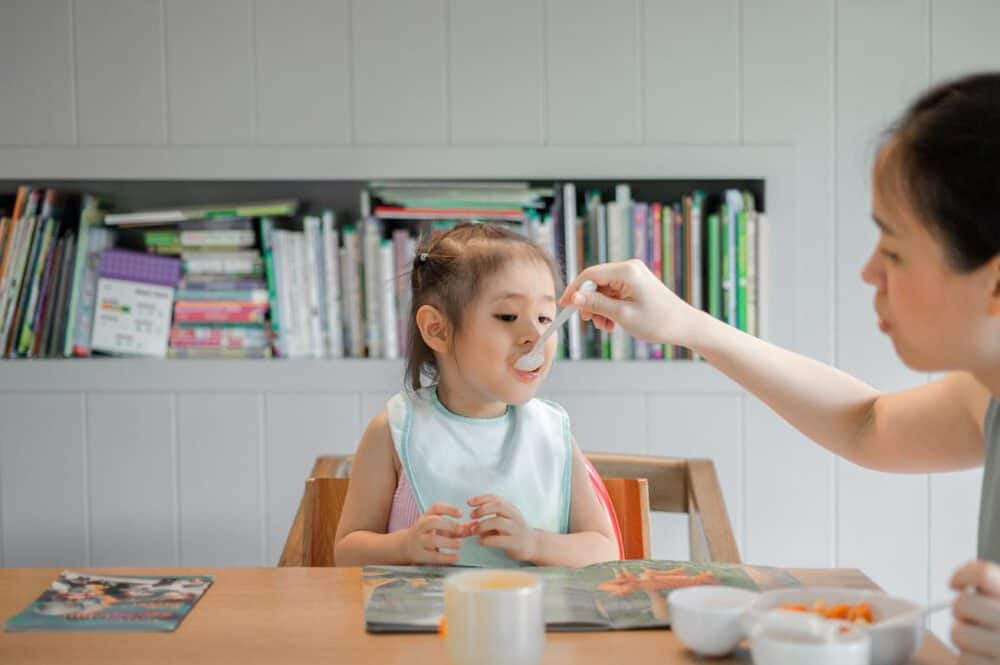 photo of mom feeding child with a spoon at the dinner table