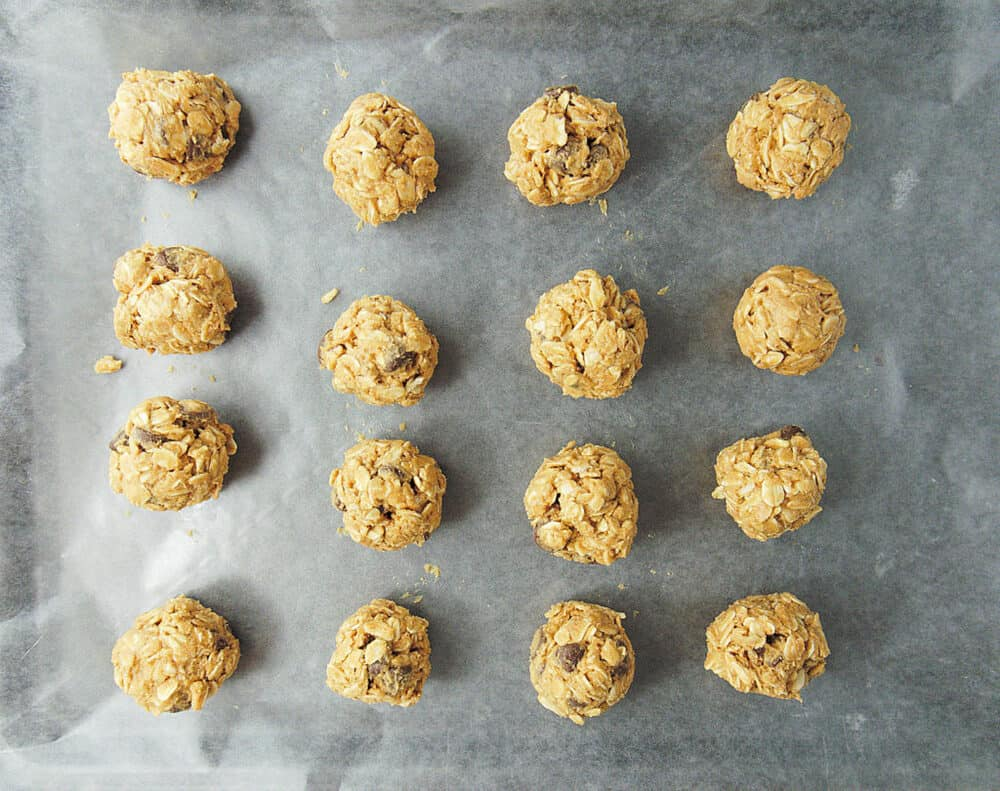 No Bake Peanut Butter Balls placed on a parchment paper on a baking sheet