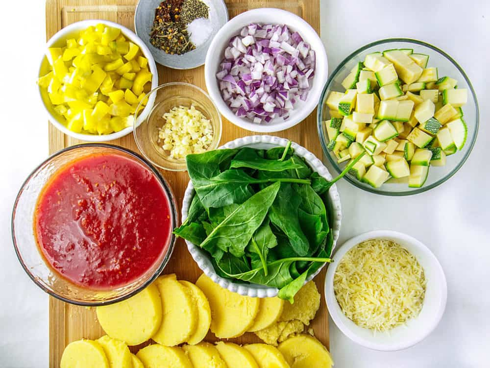 ingredients for Gluten Free Lasagna with Polenta and Vegetables: sliced polenta, tomato sauce, zucchini, peppers, spinach, onion, spices, garlic and cheese