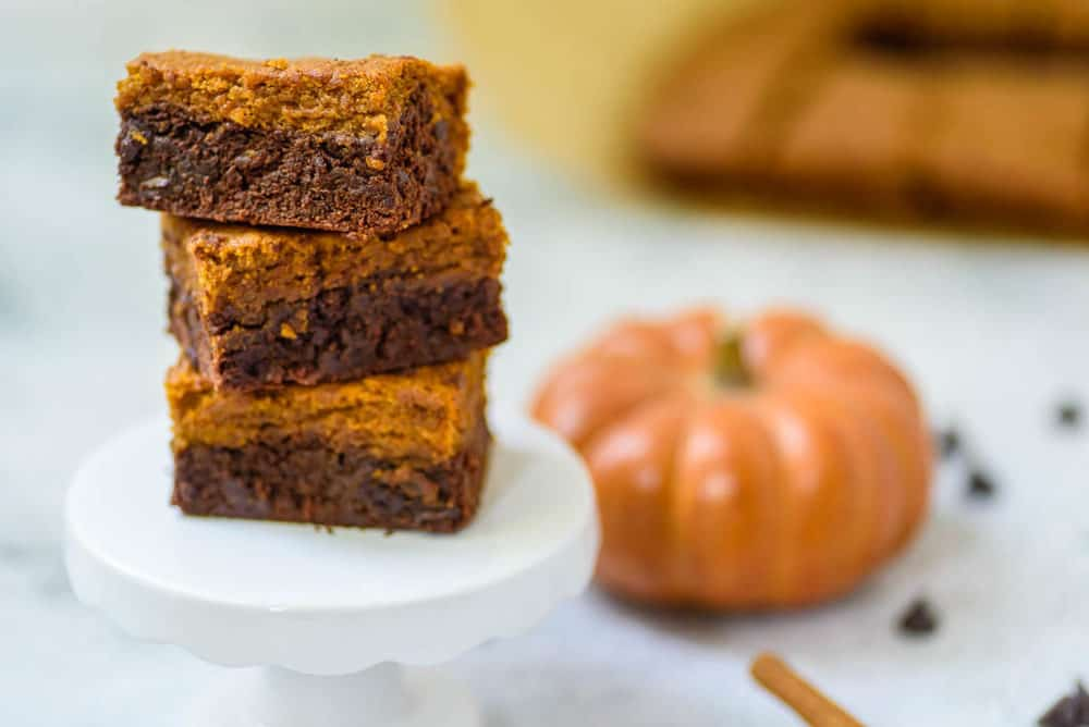 layered pumpkin brownies stacked on a white pedestal, with cinnamon, chocolate chips and pumpkin in the background