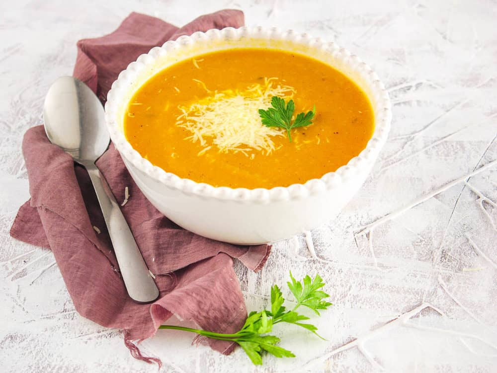 vegan butternut squash soup topped with parmesan and fresh herbs, served in a white bowl