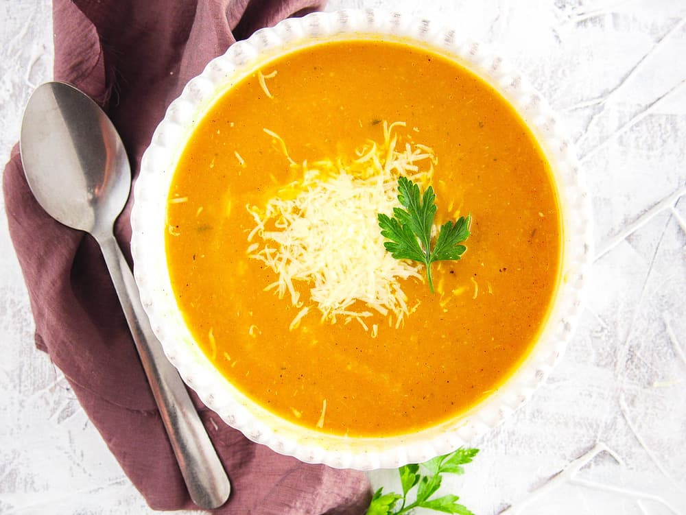 vegan butternut squash bisque topped with parmesan and fresh herbs, served in a white bowl, top view