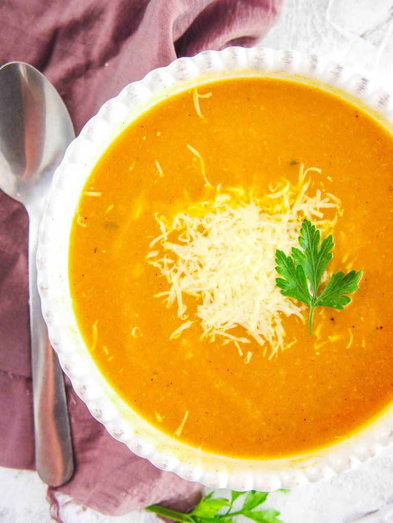 vegan butternut squash soup topped with parmesan and fresh herbs, served in a white bowl, top view