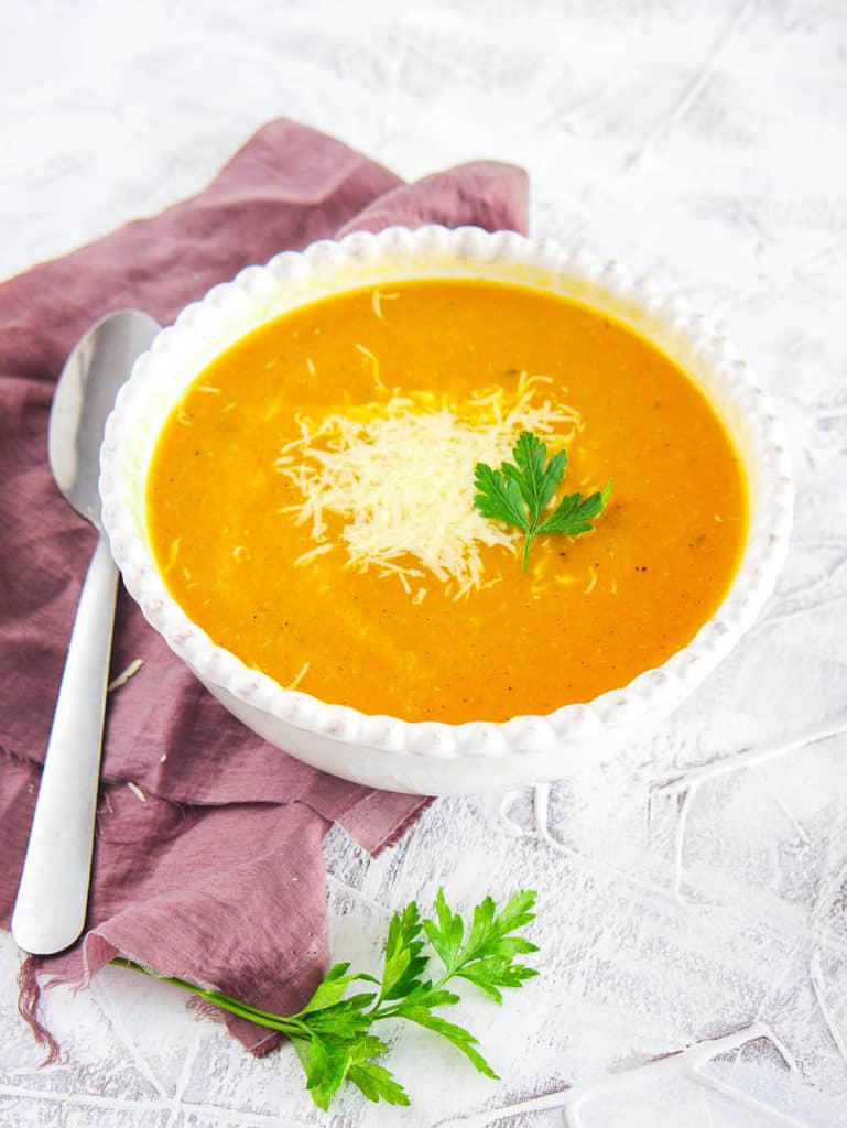 butternut squash bisque topped with parmesan and fresh herbs, served in a white bowl