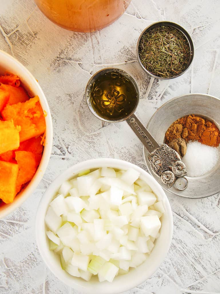 ingredients for butternut squash bisque: spices, onion, garlic, butternut squash