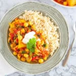 chickpea and potato curry served in a grey bowl, with brown rice on the side.