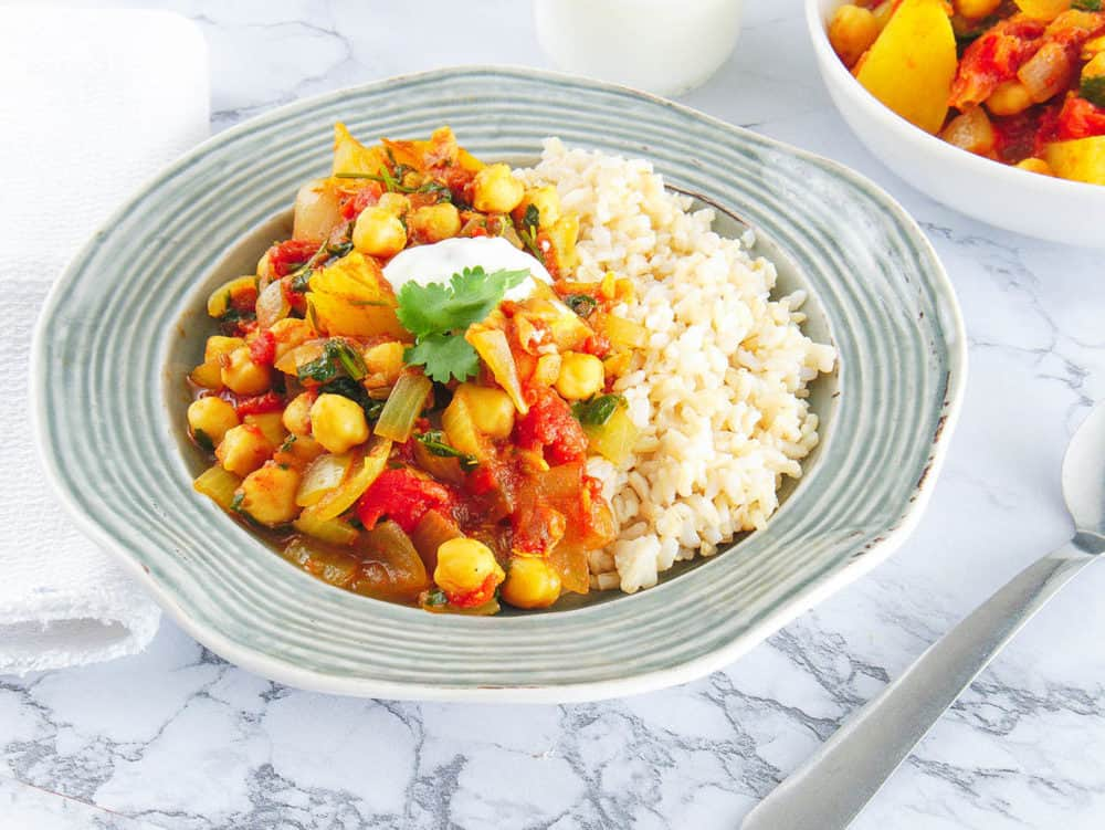 chickpea and potato stew served in a grey bowl with brown rice on the side