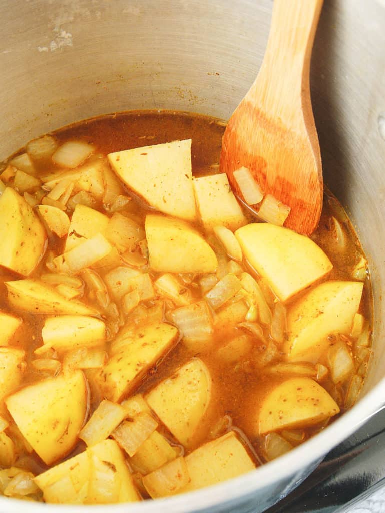 potatoes added to spice mixture in pot
