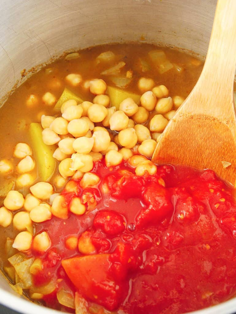 chickpeas and tomatoes added to pot